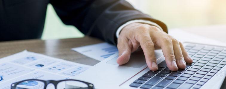 Responsabile ufficio acquisti al pc che valuta il risparmio con la soluzione di Spend Analysis di Online Procurement